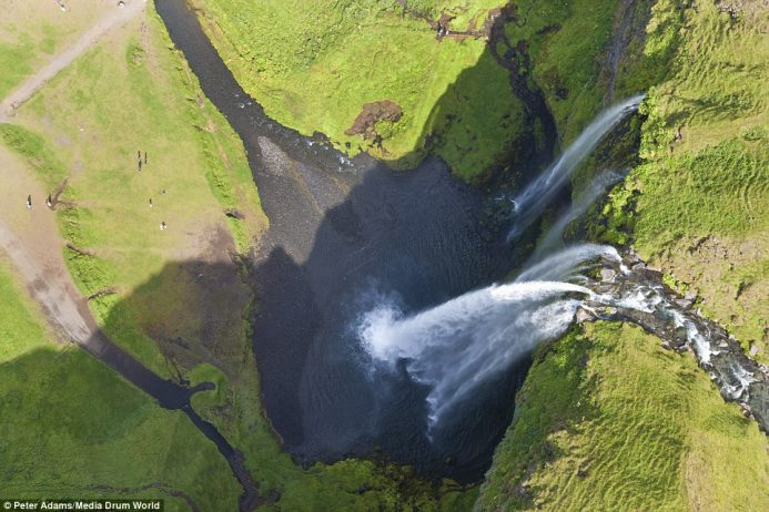 From above, the 200-ft Seljalandsfoss waterfall in Iceland looks stunning and tourists look like ants