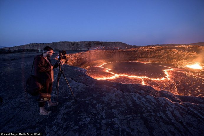 A visitor mounts his camera on a tripod in a bit to capture the volcano in its full glory while a small group of tourists line the other side