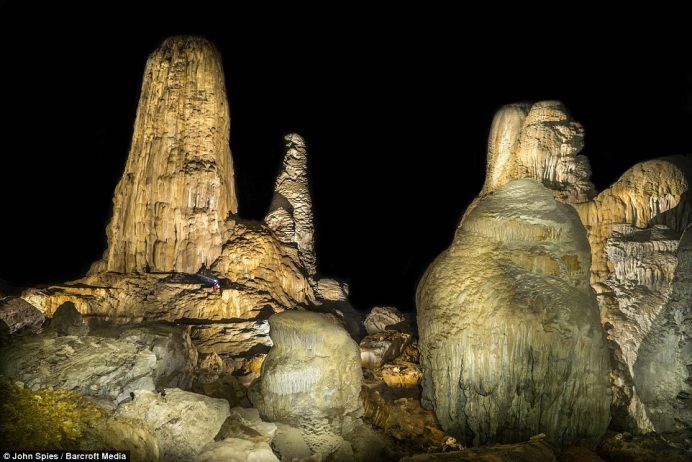 A cave explorer amongst giant stalagmites in the Stairway to Heaven area of the cave. The cave is formed by the Xe Bang Fai river, a major tributary of the Mekong