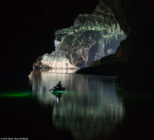 Heading into darkness, a visitor paddles a small canoe near the downstream entrance. In the dry season from November to April, the water is clear and deep with a rich green hue