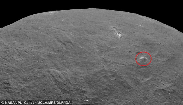 Nasa scientists in California revealed images from the Dawn spacecraft. One shows a mountain the size of Mont Blanc in a relatively flat area, circled in this image.