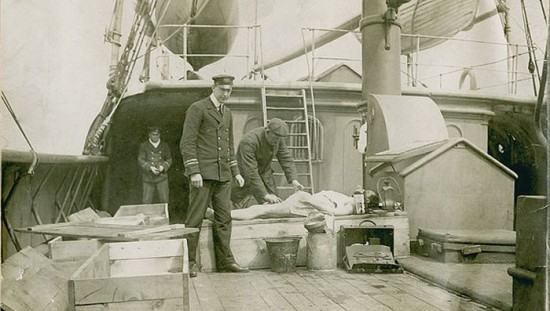 Body of RMS Titanic victim aboard rescue vessel CS Minia being made ready for makhift coffin. 1912