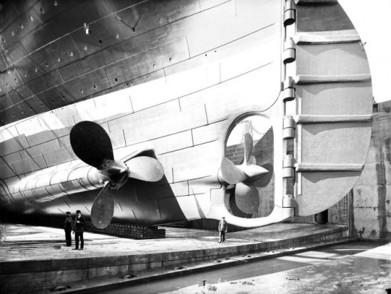 The Titanic in dry dock. Here you can see the scale of the person standing next to one of the propellers, 1912