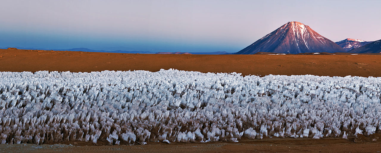 An icy forest of penitentes cluster in the foreground