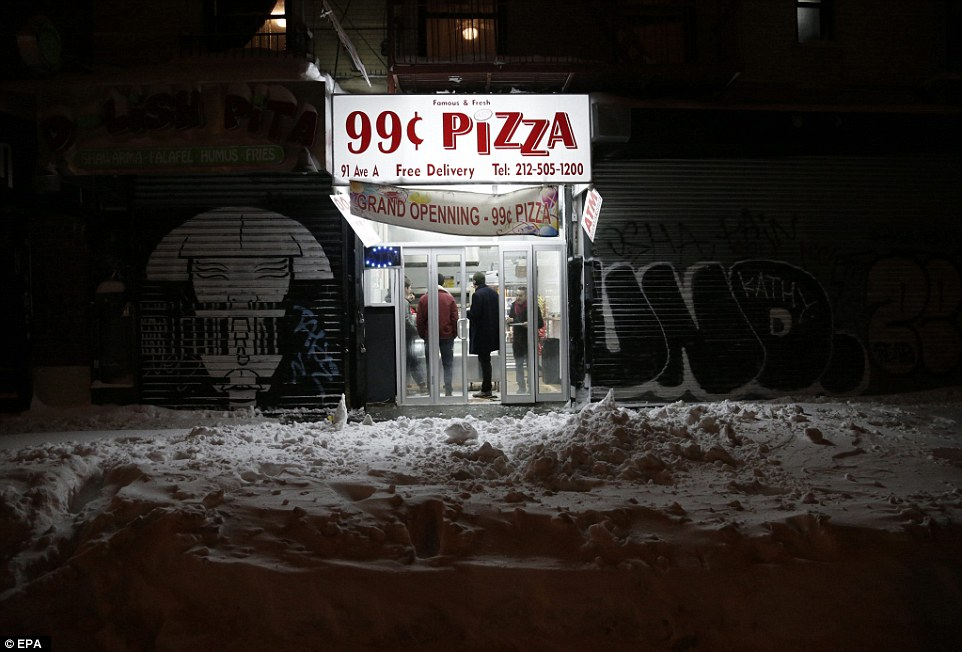A local pizza store is seen open for business in the East Village in Manhattan during a large winter storm in New York, New York
