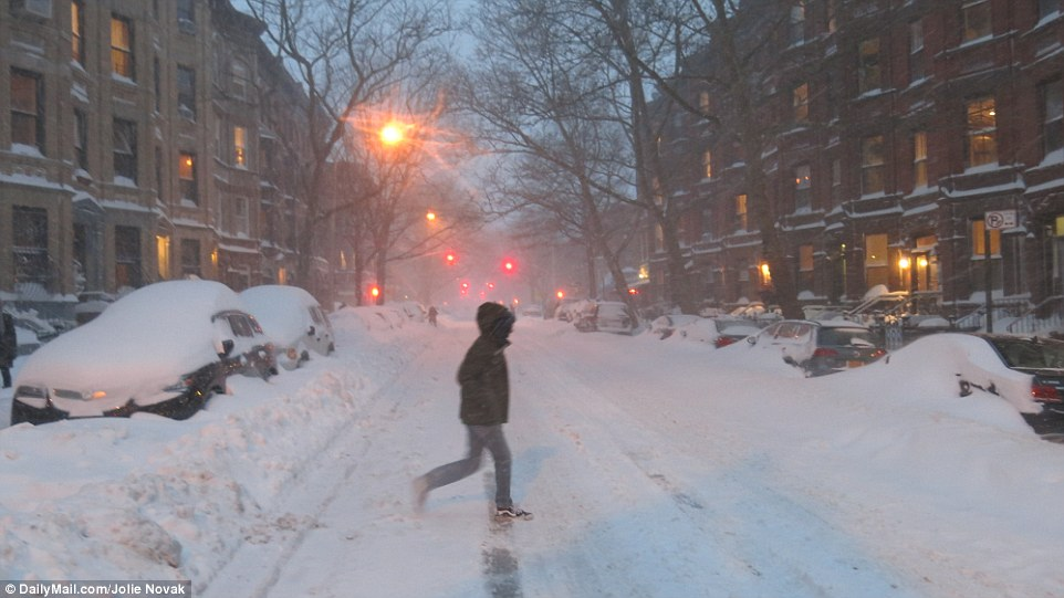 A man walks across a snow-covered street in New York City during storm Jonas on Saturday night