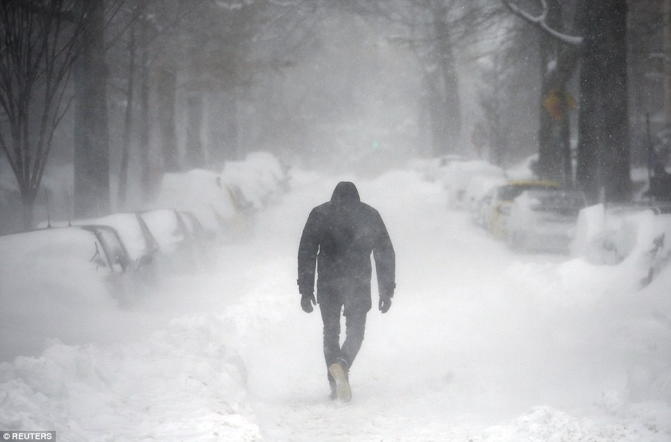 A man, wearing boots, gloves and a hooded jacket, walks along a street covered by snow during a winter storm in Washington