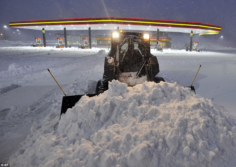 A plow clears the parking lot at the Rutters Farm Store along the Susquehanna Trail in York, Pennsylvania, on Saturday