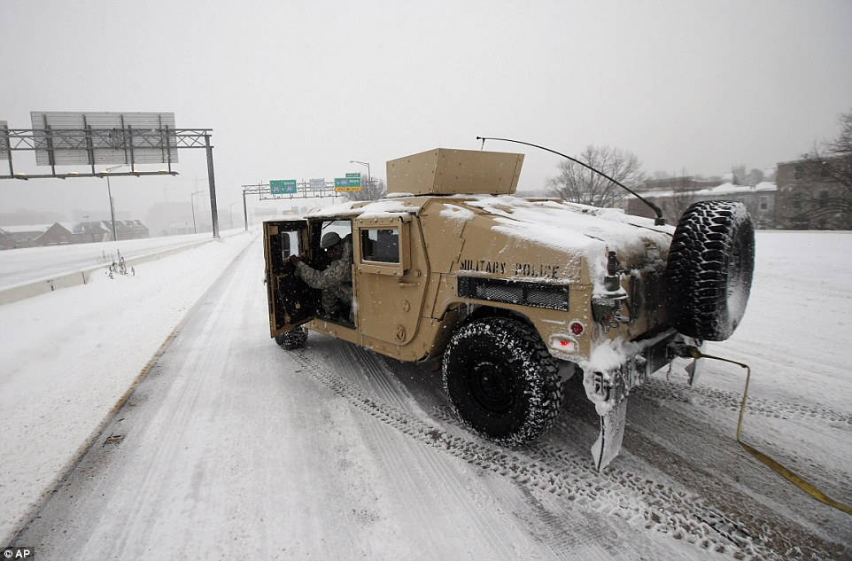 A soldier with the 275th Military Police company in a Humvee stops on I-395 as they assist a stranded motorist in the snow in Washington