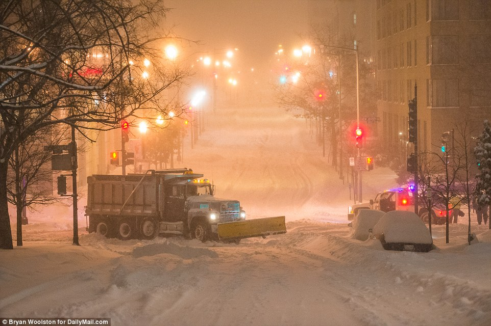 A stuck snow plow blocks an intersection on New Jersey Ave in Washington, D.C., on Saturday after the city faced at least two feet of snow
