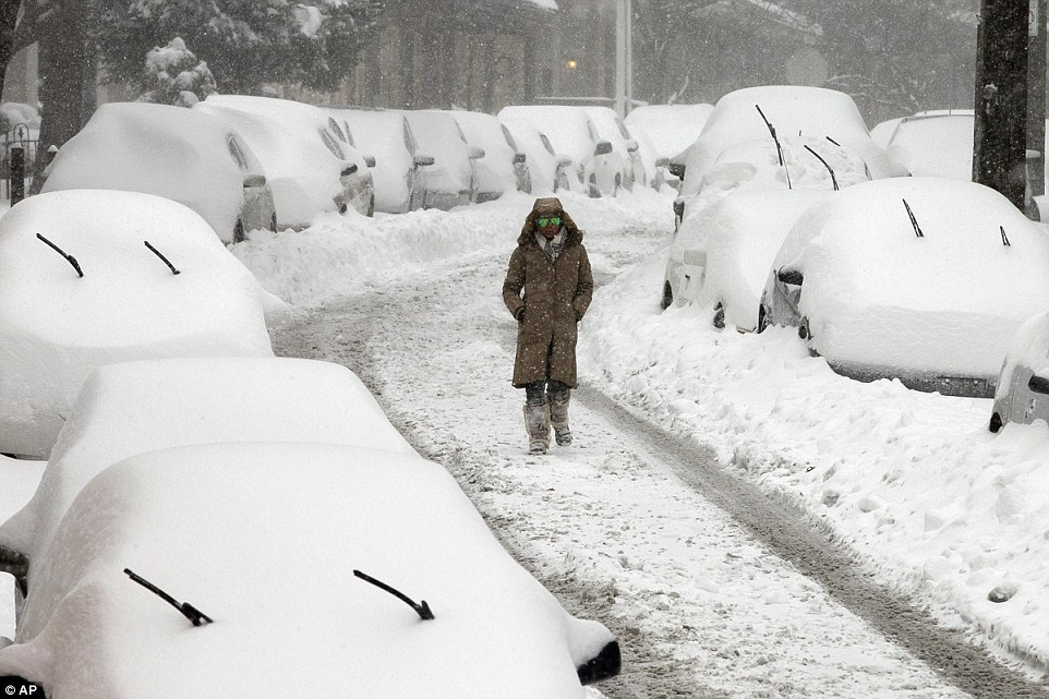 A woman walks along a street in the East Falls section of Philadelphia on Saturday after a blizzard with hurricane-force winds brought much of the East Coast to a standstill