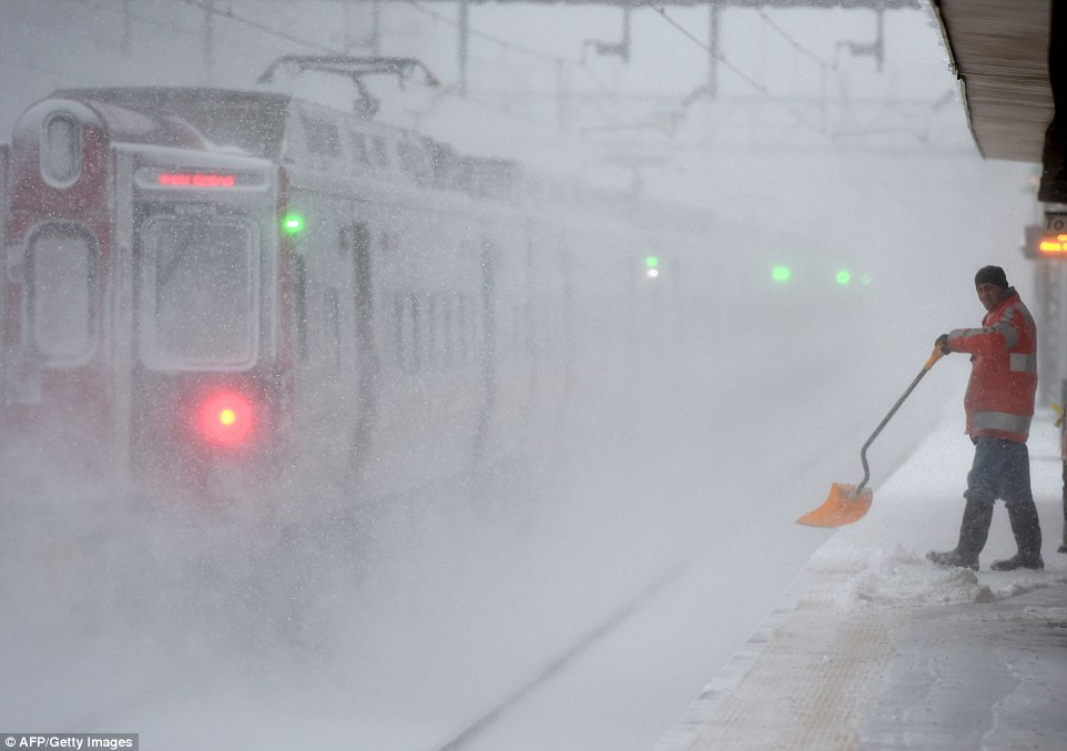 A worker cleans snow off the platform at the Metro North Train station in Greenwich, Connecticut, where heavy snow fell on Saturday