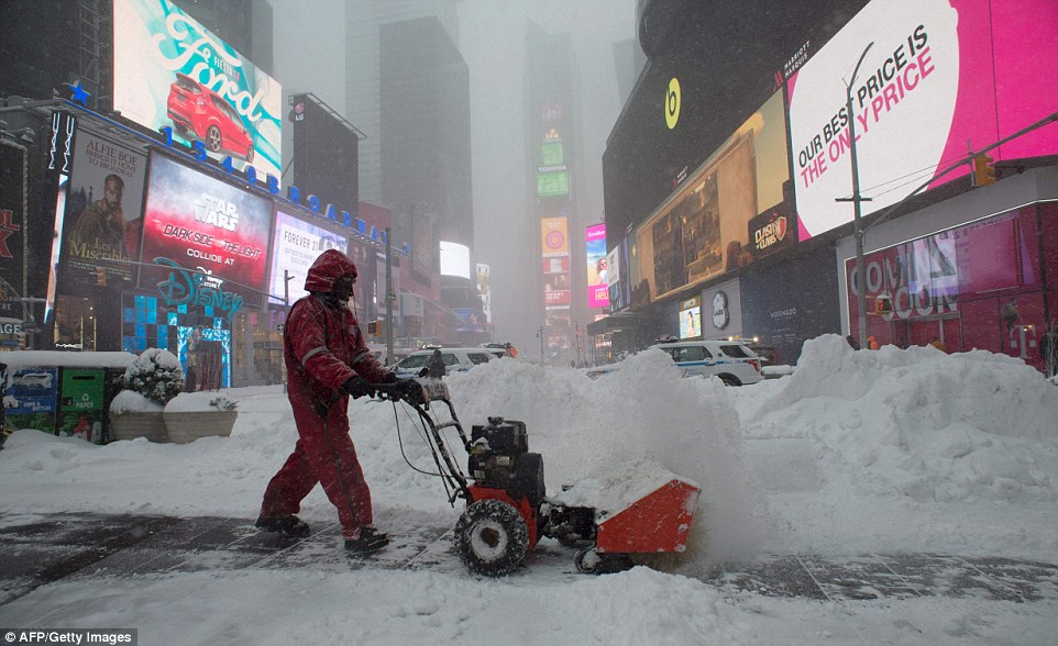 A worker in Times Square tires to keep sidewalks open on Saturday as a deadly blizzard with bone-chilling winds and potentially record-breaking snowfall slammed the East Coast