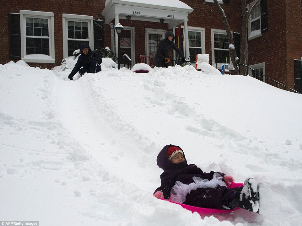 Issabella Rickman slides down a hill on a sled during a blizzard in Arlington, Virginia on January 23, 2016.