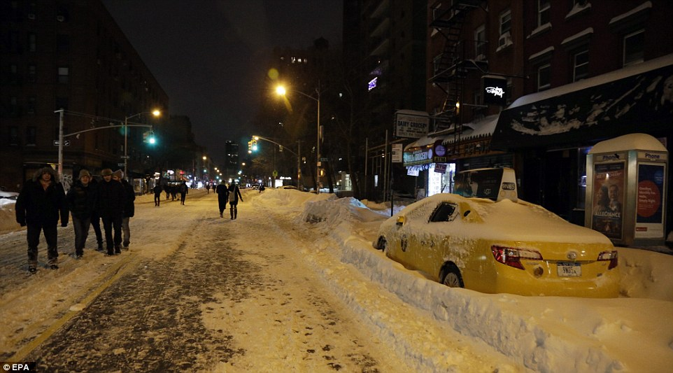 Pedestrians are seen walking on the snow-covered streets of the Lower East Side of Manhattan in New York as Storm Jonas hit the city