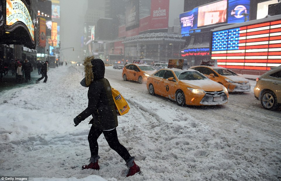 Pedestrians cope with snow covering sidewalks and streets in Time Square as the city filled with snow from storm Jonas tonight