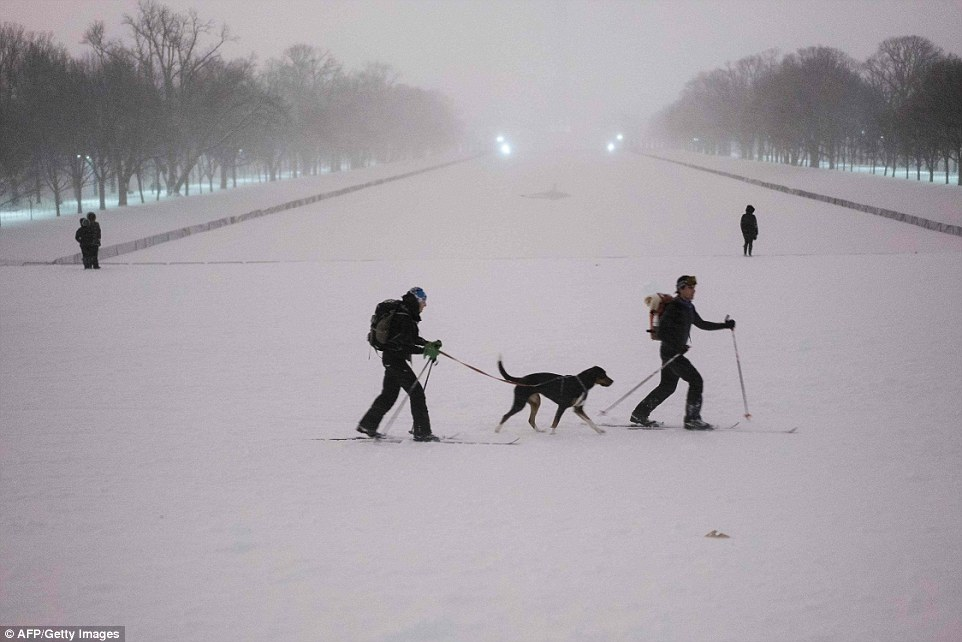People cross-country ski past the Reflecting Pool on the National Mall after a snowstorm on Saturday after snow blanketed the city