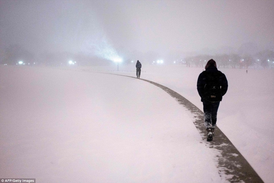 People use a wall surrounding the Washington Monument to walk above the snow after the snowstorm on Saturday