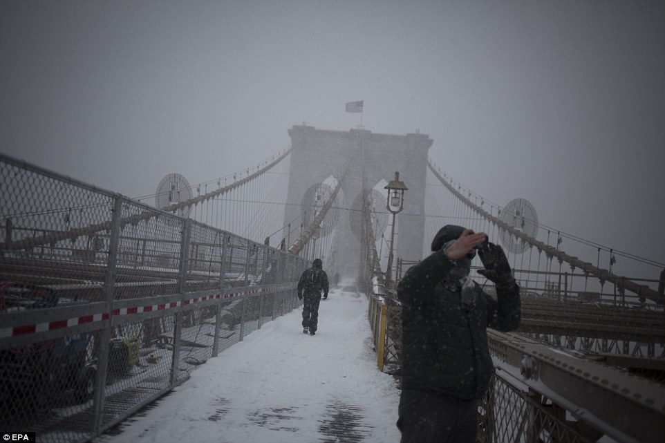 People walk across the Brooklyn Bridge in Brooklyn, New York, on Saturday during the blizzard brought on by Storm Jonas