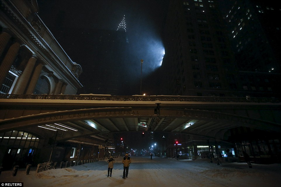 People walk down the middle of 42nd Street past Grand Central Terminal in the Manhattan borough of New York on Saturday night