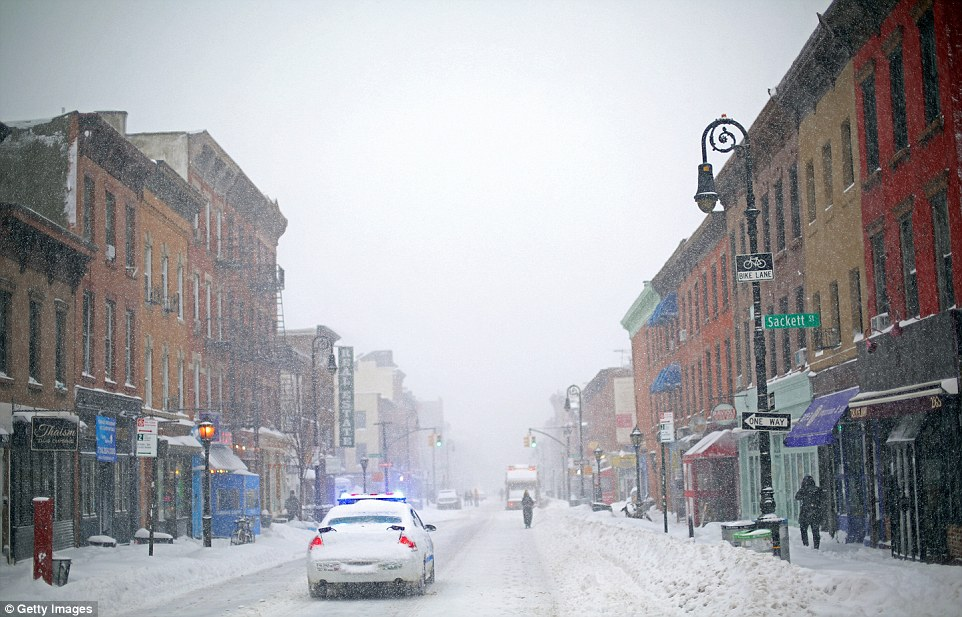 Police car patrols the in the snow on Saturday in the Brooklyn borough of New York City.