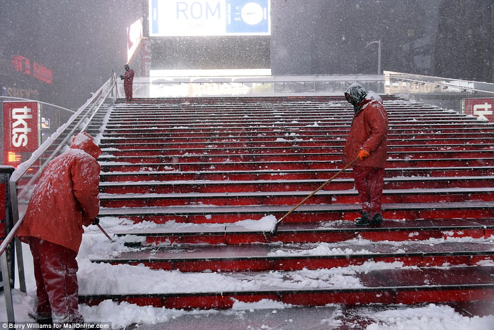 Times Square Alliance workers shovel snow off the viewing steps as New York hunkers down under storm Jonas which hit on Saturday