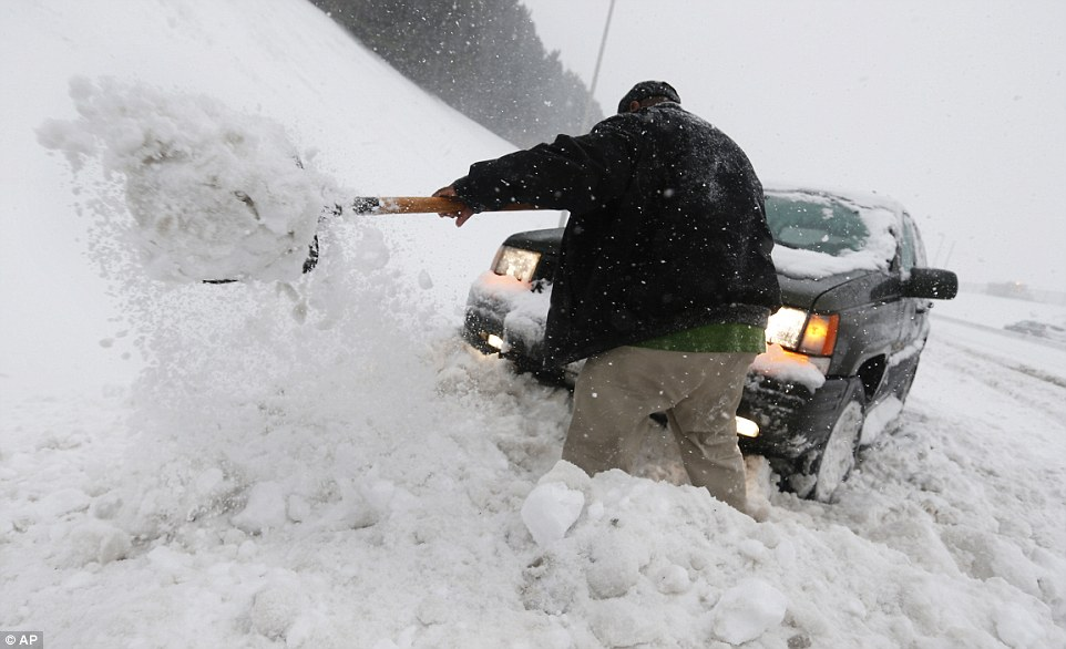 William Winston of Richmond digs his jeep out of a snow bank in Richmond, Virginia, on Saturday. Portions of the city are under blizzard warning