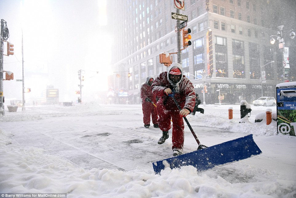 Workers struggle to keep the streets open in New York where all driving has been banned as a precautionary measure on Saturday