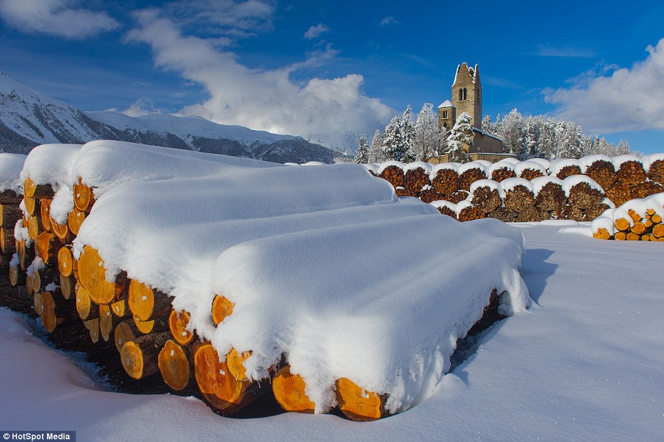 Brown log piles in front of a church stand out dramatically against the untouched snow in Celerina
