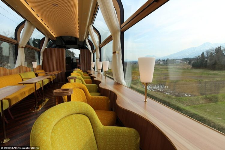 The train features armchair-style seating that faces out towards the mountains nearby