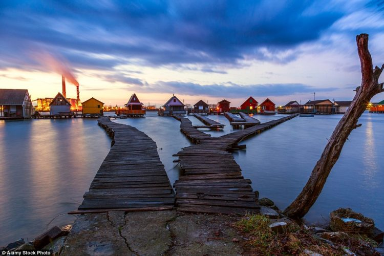 Visitors can wander through labyrinthine, coloured huts that are connected to the land by a series of boardwalks