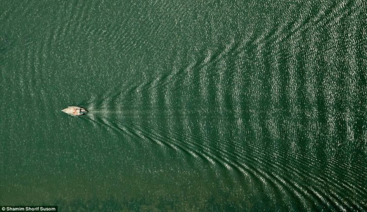 A boat cuts through the water in a photo titled 'Arrowhead'. Susom said he is revisiting his childhood through his work
