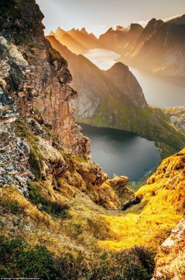 A lake in the mountains above an ocean surrounded by mountains, in Lofoten