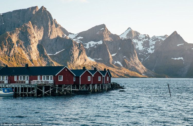 Fishermen's hut in front of mountains, surrounded by the Atlantic ocean in Lofoten - an archipelago and a traditional district in the county of Nordland, Norway
