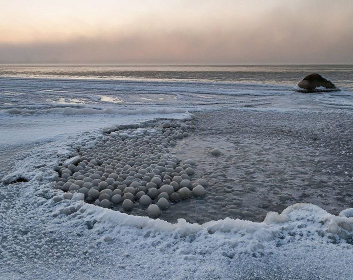 Thus, the Ice balls range from a few inches to more than feet across. So, the ice balls form when chunks of ice break off the huge ice sheets that coat parts of the lake in the winter, and as the waves toss the ice blocks around the lake