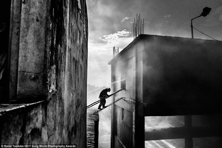 A firefighter crosses into a burning building to douse fire at Tampaco Foils Limited, a packaging factory in the Tongi industrial area near Dhaka, Bangladesh