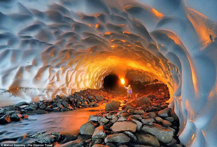 The walls and ceiling of the frozen world are made up of layers of compacted snow, with the river softly gurgling through a long chamber here illuminated by a yellow flare