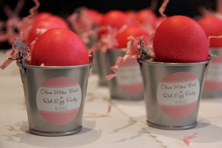 Chinese red eggs are bright pink colored cooked chicken eggs. The eggs are first hard boiled and then a wet red calligraphy paper is wiped over the eggs to create a pink coloring.
