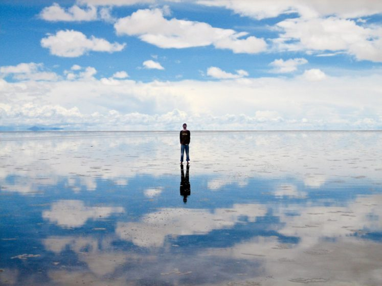 Salar de Uyuni salt flats in Bolivia are covered in a thin layer of water, creating surreal reflections of the sky.