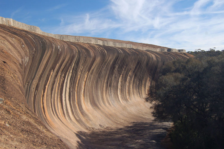 """The wave rock is about 15 meters high and about 110 meters long. Wave Rock is a remarkable example of what geomorphologists call a """"flared slope""""."""