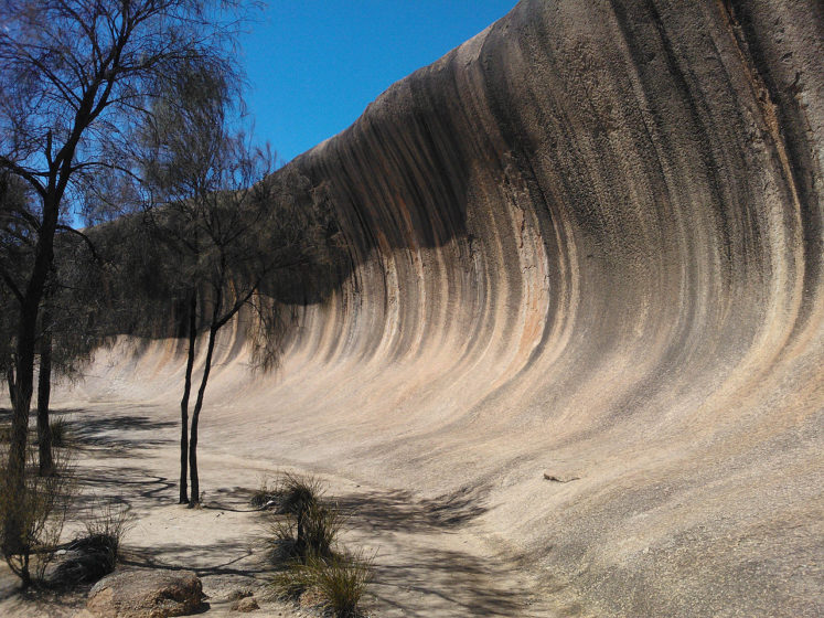 The shape of the rock is not caused by a wave phenomenon, rather its rounded wave-like shape was formed by subsurface chemical weathering