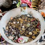 Visitors leave coins and trinkets at several of the doll shrines found inside some of the Island's buildings
