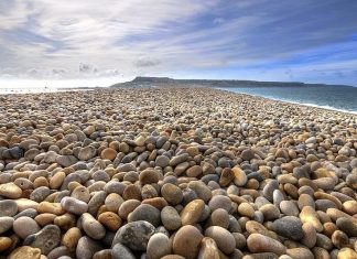 "The English Chesil Beach ""Chesil Bank""lies in the county of Dorset. It is popular for its pebbles stretched 18 miles (28 kilometers) long and north-west from Portland to West Bay."