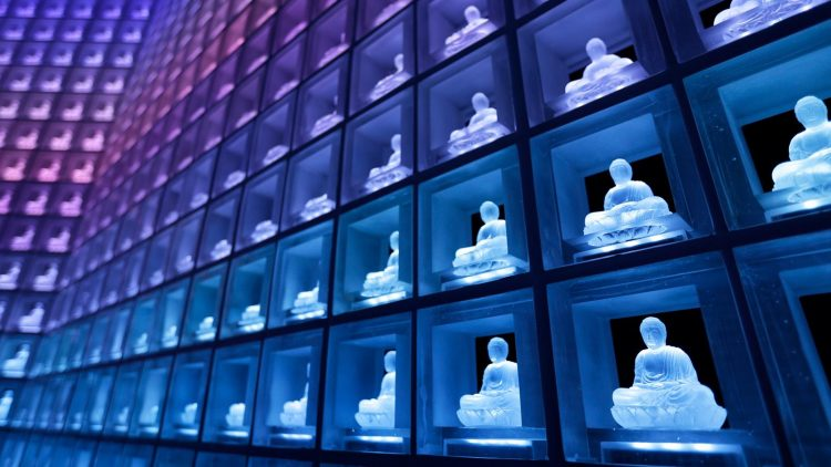 In facilities like this one in Japan, ashes are kept in urns behind glowing buddhas - allowing many people to be laid to rest in one room